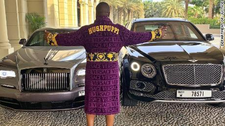 """A social media influencer known as """"Hushpuppi"""" poses with two luxury cars."""
