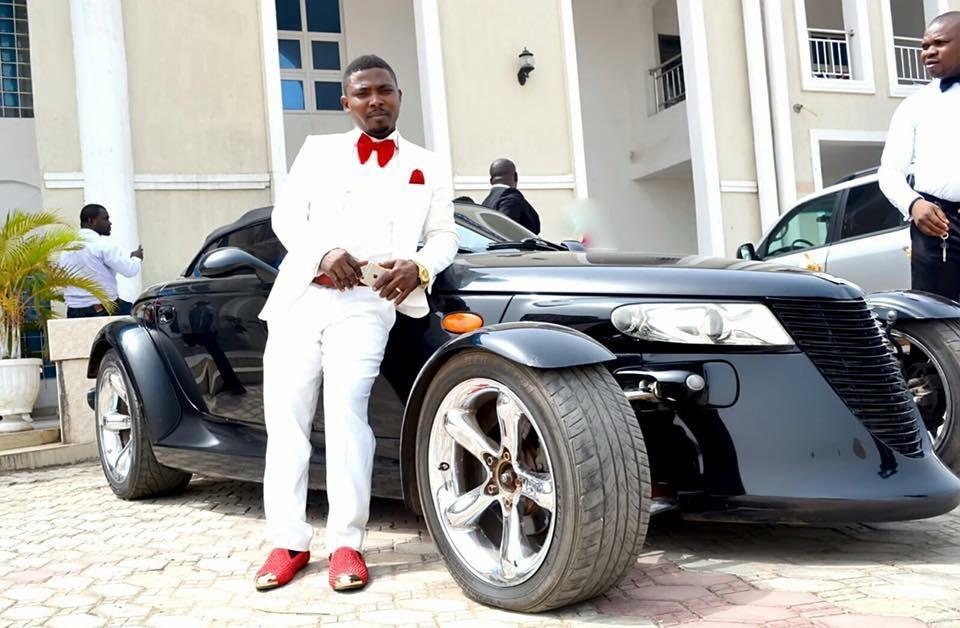 """Onuegwu Ifeanyi, also known as """"SSG Toolz,"""" poses next to a Plymouth Prowler."""